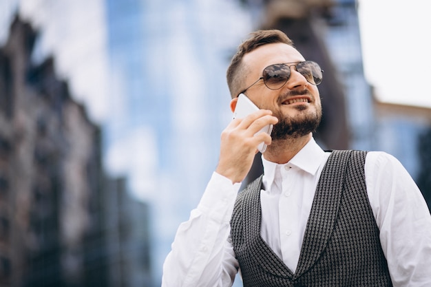 Successful business man by the skyscraper talking on the phone