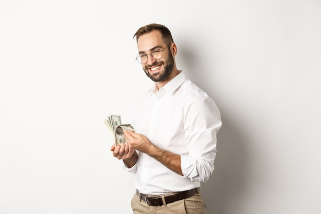 Successful business man counting money and smiling, standing against white background and looking satisfied.