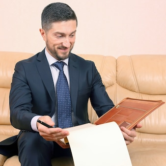 가죽 소파에 앉아 비즈니스 문서에 종사하는 성공적인 사업가