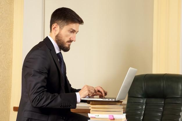 노트북을 사용하는 사무실에서 성공적인 사업가