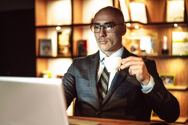 Successful business man reads news. middle aged male person looks on laptop screen drinking
