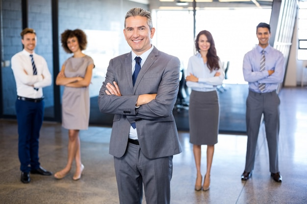 Successful business man smiling  while his colleagues standing behind him in office
