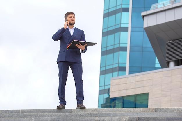 성공적인 사업가는 문서를 손에 들고 사무실 비즈니스 건물의 배경에 대해 계단에 서 있습니다.