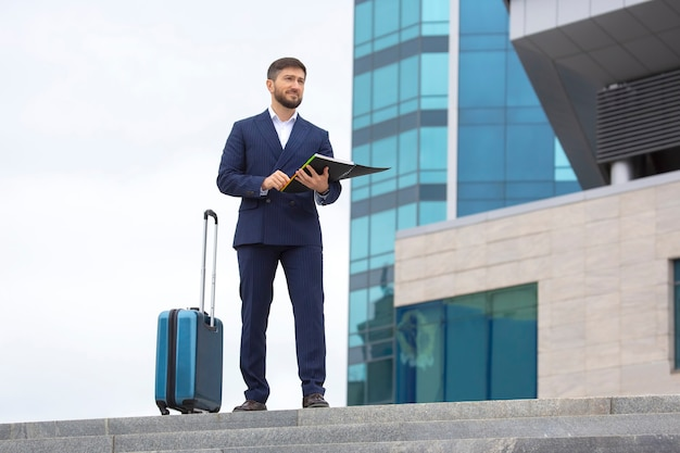 Successful business man stands on the steps against office business building with documents in his hands