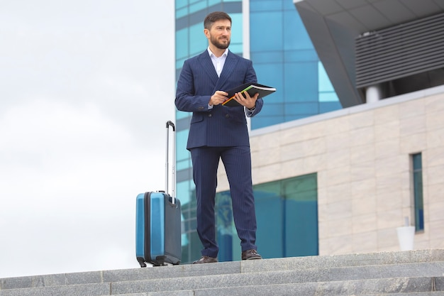 Successful business man stands on the steps at office building with a project business documents in his hands