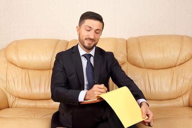 Успешный деловой человек с деловыми документами, сидя на кожаном диване