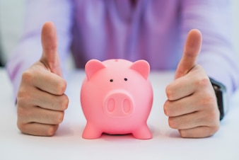 Successful business man with piggy bank holding thumbs up in office