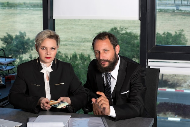 Successful business man and woman count money in modern office. caucasian lady counting money at the table. bearded businessman in black suit. business couple working, talking together on project