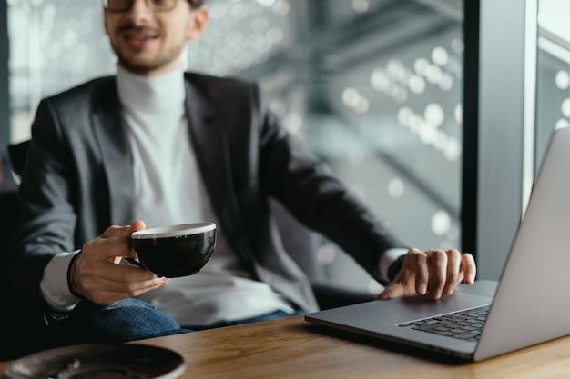 コーヒーを飲みながらノートパソコンで作業する成功するビジネス人