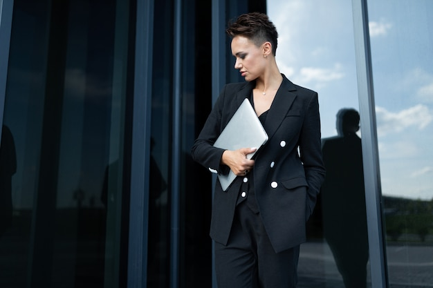 Successful business owner posing of office building
