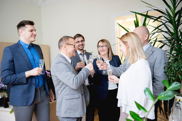 Successful business people are clinking glasses of champagne and smiling while celebrating in office