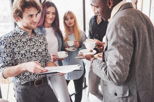 成功したビジネス人々はガジェットを使用して、オフィスでのコーヒーブレーク中に話して笑顔