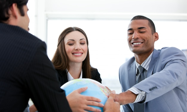 Successful business people having a meeting around a terrestrial globe