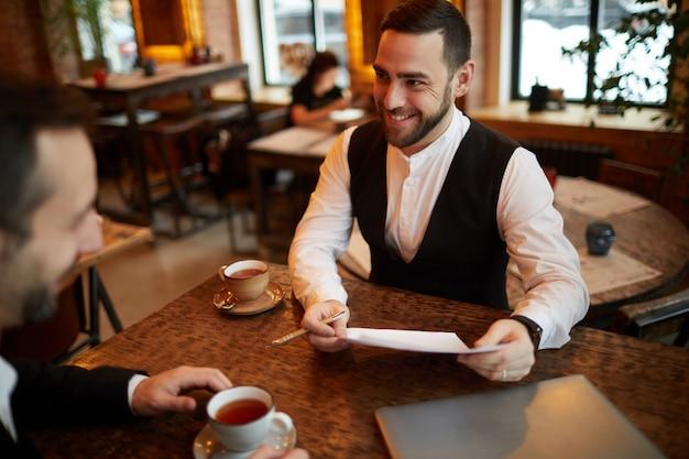 Успешные деловые люди обсуждают сделку в ресторане