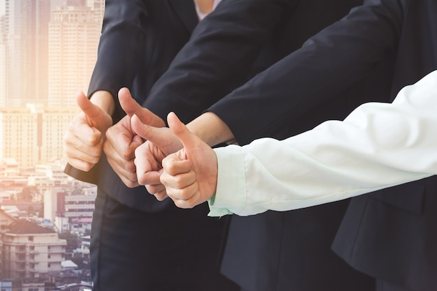 Successful business people with thumbs up, business team