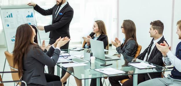 사무실의 직장에서 새로운 프로젝트 발표에 대해 재무 관리자에게 박수를 보내는 성공적인 비즈니스 팀