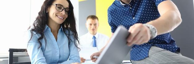 Успешная бизнес-команда обсуждает новые стратегии в офисе на ноутбуке