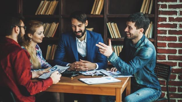 Успешная бизнес-команда обсуждает финансовый отчет о прибыли компании на рабочем месте в офисе