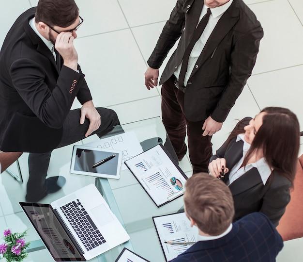 사무실의 직장에서 회사의 새로운 재무 계획을 논의하는 성공적인 비즈니스 팀