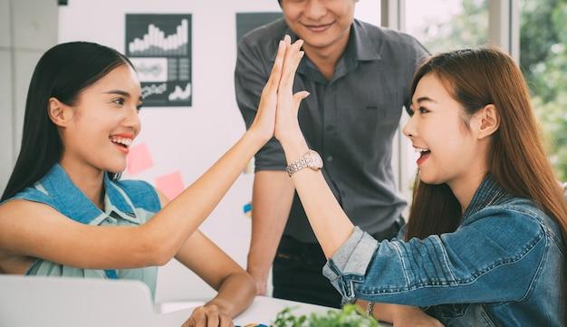 Успешная бизнес-команда, дающая привет-пять в офисе modren