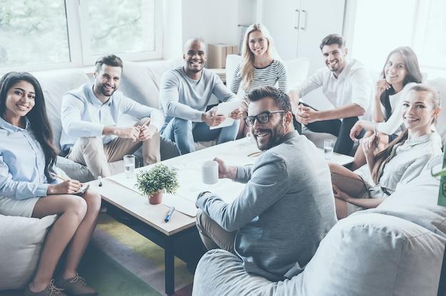 성공적인 비즈니스 팀입니다. 사무실 책상에 함께 앉아 미소를 지으며 카메라를 바라보는 자신감 있는 젊은 사업가들