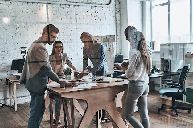 Успешная бизнес-команда. группа молодых современных людей в элегантной повседневной одежде обсуждает бизнес, стоя за стеклянной стеной в творческом офисе