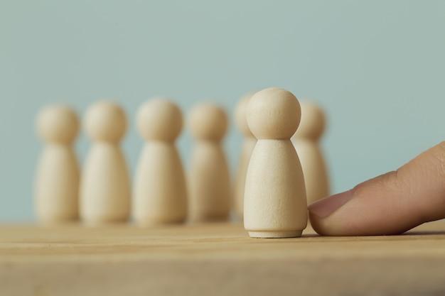 Успешная бизнес-команда лидер концепции: рука выбирает деревянные фигуры человека и людей, выделяющихся из толпы. изображает управление человеческими ресурсами и найма сотрудника или найма.
