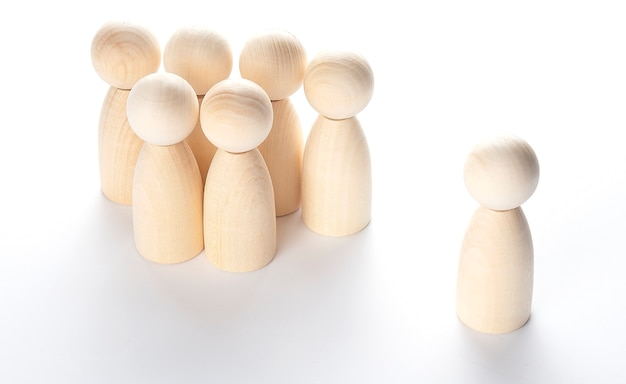 Successful business team leader concept: wooden figures of man and people standing out from the crowd.