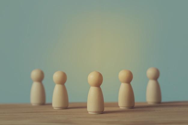 Успешная бизнес-команда лидер концепции: деревянные фигуры человека и людей, выделяясь из толпы.