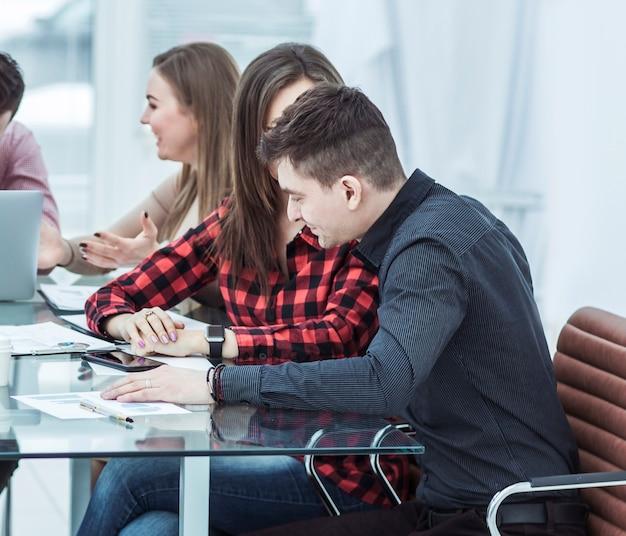 현대 사무실의 책상에 앉아 있는 성공적인 비즈니스 팀
