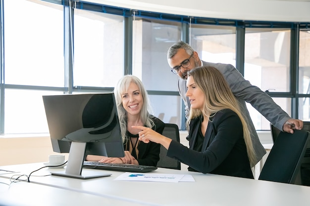 Successful business team watching content on computer monitor together, discussing project, sitting at workplace and pointing at display. business communication or teamwork concept