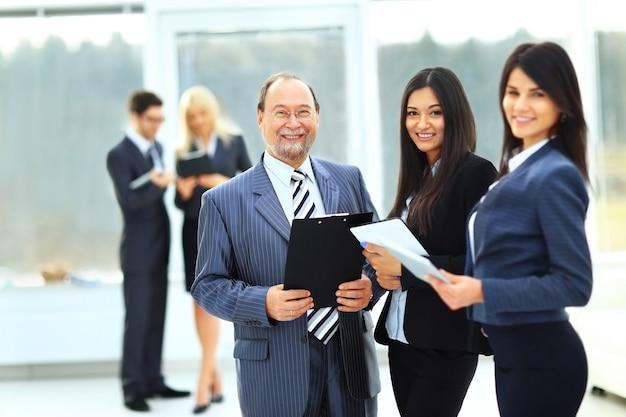 オフィスの背景にドキュメントを持つ成功したビジネスチーム
