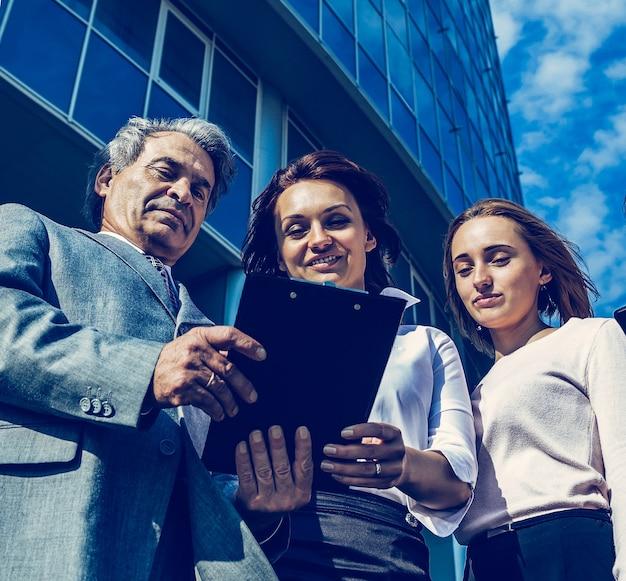 Успешная бизнес-команда с планшетами на фоне в выключенном состоянии