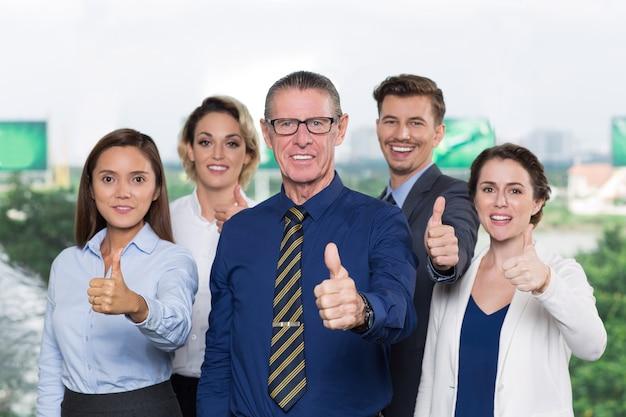Riuscita squadra di affari con i pollici in su sorridente