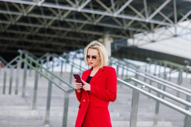ビジネスセンターの高層ビルの背景に取り引きを交渉しているスマートフォンで話している赤いコートで成功したビジネスウーマン。