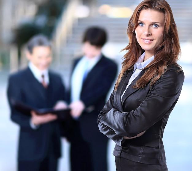 Успешная деловая женщина выглядит уверенно и улыбается