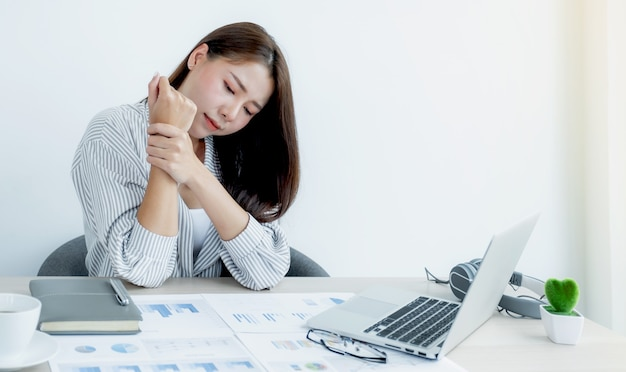 A successful business woman sitting in the office using a laptop to work so hard that it sore her wrists.