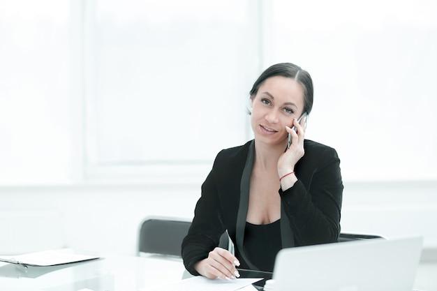 Успешная деловая женщина разговаривает на смартфоне в своем офисе.