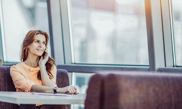 Успешная деловая женщина разговаривает по смартфону сидя