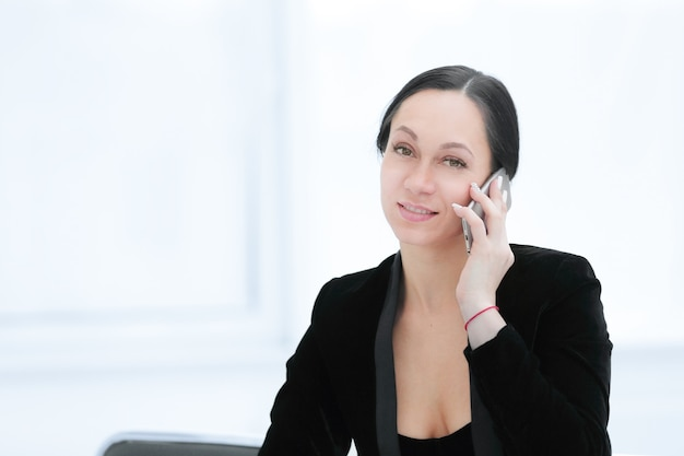 Successful business woman talking on smartphone in her office.