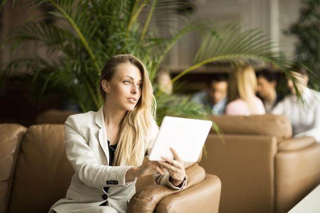 Успешная деловая женщина с цифровым планшетом, сидя на диване