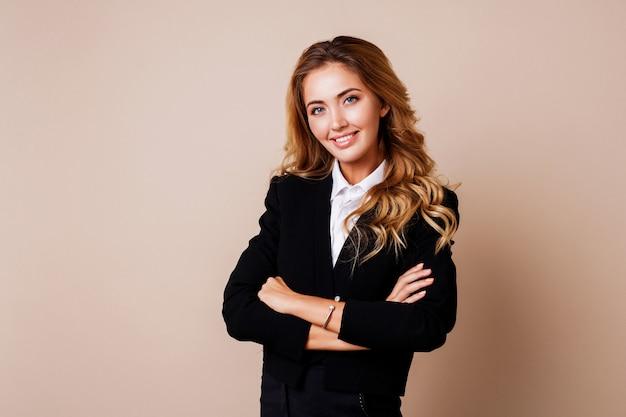 Успешная деловая женщина с откровенной улыбкой и скрещенными руками в стильном костюме на бежевой стене.