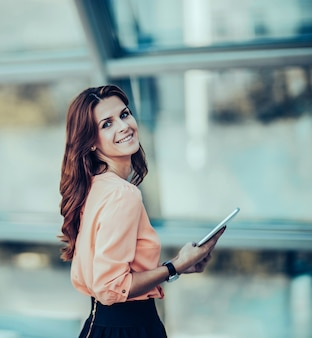 Успешная деловая женщина с цифровым планшетом, стоящая возле а-ля