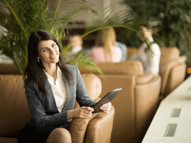 Успешная деловая женщина с документами, сидя в кресле