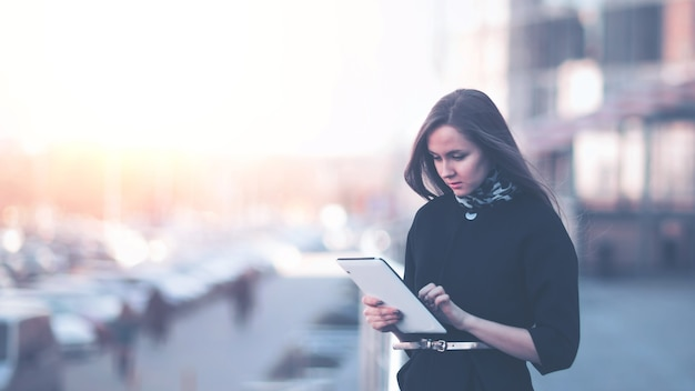 Successful business woman working on a digital tablet near an office building