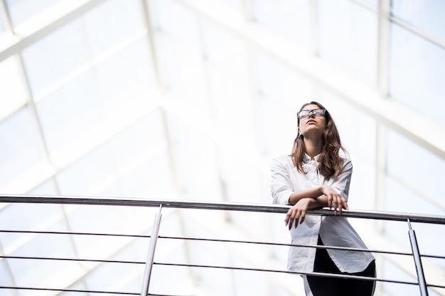 白いtシャツを着たモダンなオフィスセンターのバルコニーを見渡して立っている成功したビジネス女性