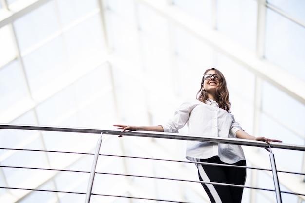 흰색 티셔츠를 입고 현대 사무실 센터에서 발코니를 통해 찾고 서 성공적인 비즈니스 여성
