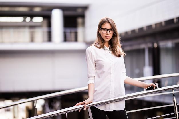成功したビジネスの女性が休んで立っていると白いtシャツを着たモダンなオフィスセンターのバルコニーを見渡す