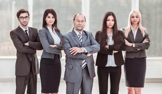 성공적인 사업가 및 비즈니스 팀이 팔과 함께 서서 그 앞에서 건넜다.