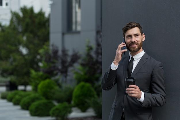 外のオフィスの近くの電話で話しているビジネススーツで成功した実業家ブローカー、昼休みの間にコーヒーを持って笑顔でカメラを見ているバンカー